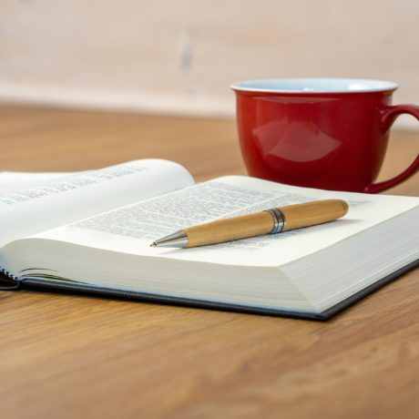 open bible with coffee cup